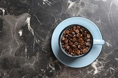 Cup with roasted coffee beans and space for text on grey background. Top view stock images