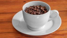 Cup of roasted coffee beans in white ceramic cup, on small white ceramic plate, on wooden surface stock photo