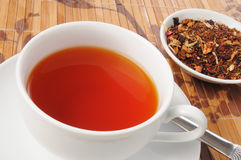 Cup of rooibos tea. A cup of honey spice rooibos tea with whole tea leaves on the side Stock Photography