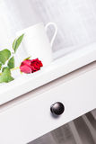 Cup and rose on white table Stock Photography