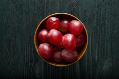 Cup of rotten grapes. Wooden cup of rotten grapes on the dark wooden table Royalty Free Stock Images