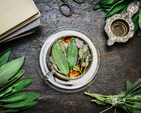 Cup of sage tea with fresh herbs leaves, books and old vintage strainer on rustic wooden background, top view. Still life royalty free stock photography