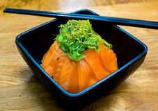 Cup of salmon sushi and green seaweed on the top Royalty Free Stock Photo
