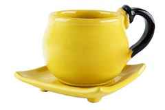 Cup and saucer. Bright yellow thick tea cup on an square saucer Royalty Free Stock Photos