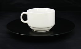 Cup and saucer on black Royalty Free Stock Photography