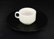 Cup and saucer on black Royalty Free Stock Image