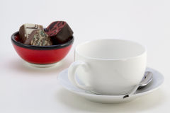 Cup with saucer and a bowl with candies Royalty Free Stock Images