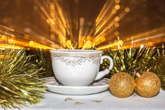 Cup on a saucer. Christmas balls and tinsel. Glowing salute from. The image of cup on a saucer. Christmas balls and tinsel. Glowing salute from bokeh over the royalty free stock photography