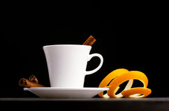 Cup with saucer, cinnamon sticks and orange skin Royalty Free Stock Image