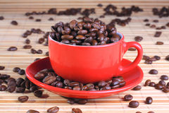 Cup on the saucer with coffee beans Stock Photos