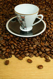 Cup with saucer on coffee beans background Royalty Free Stock Photos