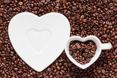Cup and saucer on coffee beans background Royalty Free Stock Images