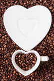 Cup and saucer on coffee beans background Royalty Free Stock Photo