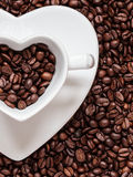Cup and saucer on coffee beans background Royalty Free Stock Image