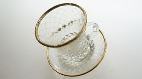 Cup on saucer. Crystal cup on a saucer with a gold kayemoy on a white background Royalty Free Stock Image