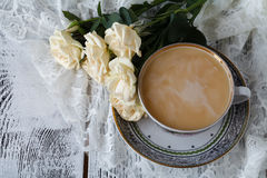 Cup with a saucer. Delicate white flowers roses. Stock Photos