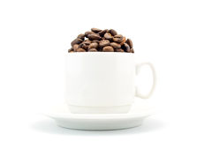 Cup on a saucer filled with coffee beans isolated on white Stock Photos