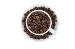 Cup and saucer, filled with roasted coffee beans Stock Image