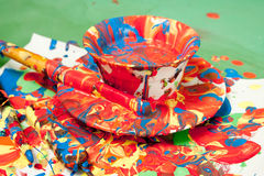 Cup and a saucer full of bright paints Royalty Free Stock Images