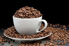 Cup and saucer full of coffee beans Stock Images
