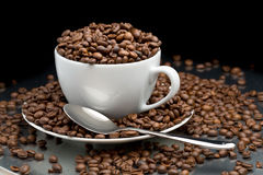 Cup and saucer full of coffee beans with a spoon Stock Image