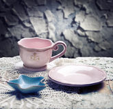 Pink cup, saucer and starfish shaped bowl on table over grunge background Stock Photo