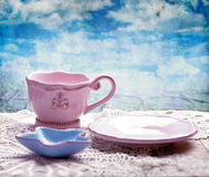 Pink cup, saucer and starfish shaped bowl on table over grunge sky background Stock Photography