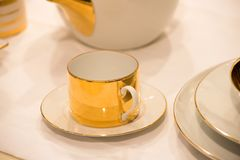 Cup on saucer served on white table cloth. Cup on saucer of porcelain with golden gilt served on white table cloth background. Tea party or ceremony concept royalty free stock photo