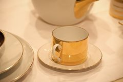 Cup on saucer served on white table cloth. Cup on saucer of porcelain with golden gilt served on white table cloth background. Tea party or ceremony concept royalty free stock photos