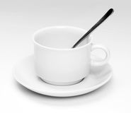 Cup and saucer with spoon. White cup and saucer with spoon inside the cup all isolated on a white background Stock Photos