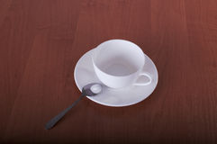 Cup and saucer with spoon. White cup and saucer with chrome spoon on wooden table Stock Images