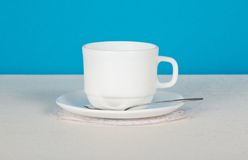 Cup, saucer and spoon on white cloth. Cup, saucer and spoon on a white cloth, on a blue background Royalty Free Stock Images
