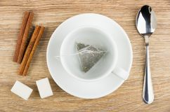 Cup with saucer, tea bag, lumpy sugar, cinnamon sticks Royalty Free Stock Image