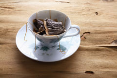 Cup and Saucer with Teabags. On Wooden Background Stock Photo