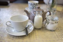 Cup and saucer with a teapot, milk and sugar. In a café setting Royalty Free Stock Photos