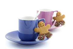 Cup and saucers with gingerbread man cookie next to it Royalty Free Stock Photos