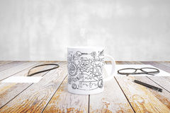 Cup with scheme print, glasses, badge and pen on wooden table Royalty Free Stock Images