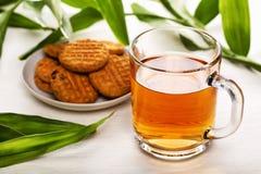 Cup schwarzer Tee und Biskuite Stockfotos