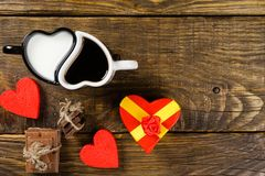Cup in the shape of hearts, one poured coffee in the other milk, next the chopped chocolate twine tied around the decorative heart royalty free stock image