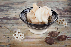 Cup of shea butter  and nuts Stock Image