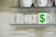 Cup on shelf with Dollar symbol Royalty Free Stock Images
