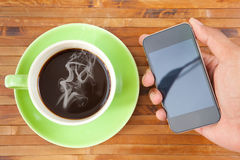 Cup and smartphone Royalty Free Stock Images
