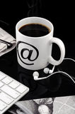 Cup of smoking hot coffee. With keyboard, headphones, newspaper, glasses, napkin over black background stock image