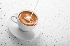 Cup of smooth coffee with poured milk Stock Photo