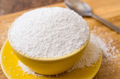 Cup of sorbitol sweetener. Cup of sorbitol, a natural sweetener on the table next to a spoon. Closeup Stock Photography
