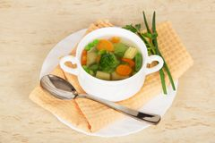 Cup with soup, spoon, parsley and green onions Royalty Free Stock Images