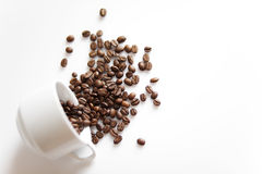 Cup with sparse coffee beans Royalty Free Stock Images