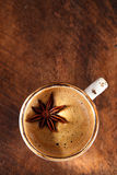 A cup of spiced coffee with anis star and cinamon sticks and sugar royalty free stock images