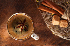 A cup of spiced coffee with anis star. And cinamon sticks and sugar Royalty Free Stock Photo