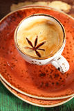 A cup of spiced coffee with anise star and saucers Stock Photos